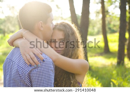 portrait of a beautiful young couple in love in the forest - stock photo