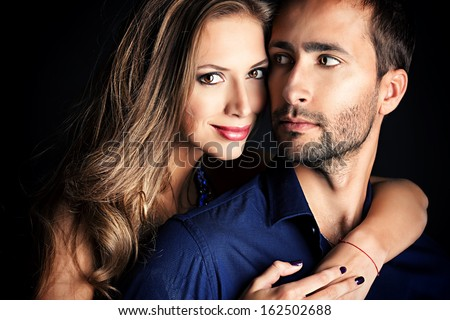 Portrait of a beautiful young couple in love posing at studio over black background. - stock photo