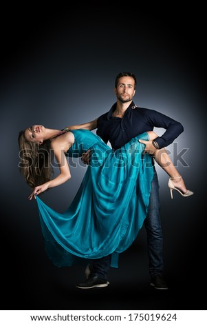Portrait of a beautiful young couple in love posing at studio over dark background. - stock photo