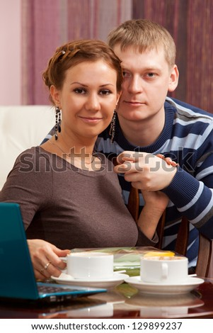 Portrait of a beautiful young couple sitting together at a table with a laptop and drinking coffee.