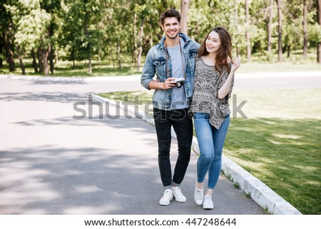 Portrait of a beautiful young couple walking in park together - stock photo