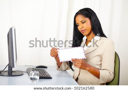 Portrait of a beautiful young executive woman at work while open a letter - stock photo