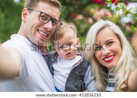 Portrait of a beautiful young family with son in nature. - stock photo