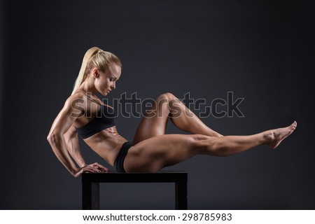 Portrait Of A Beautiful Young Female Athletes With Dumbbell In Studio
