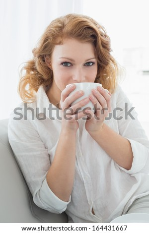 Portrait of a beautiful young female sitting on sofa and drinking coffee at home