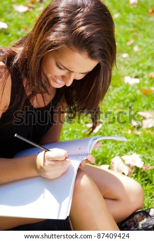 Portrait of a beautiful young female student sitting outdoor at college campus park and reading her copybook and making notes - stock photo