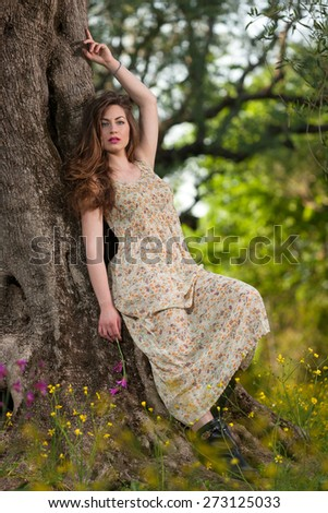 portrait of a beautiful young girl among yellow flowers in the nature