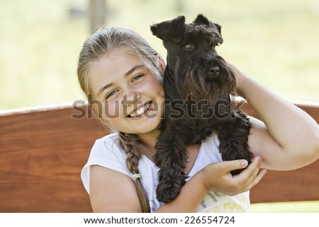 Portrait of a beautiful young girl holding her dog while enjoying a summer day - stock photo