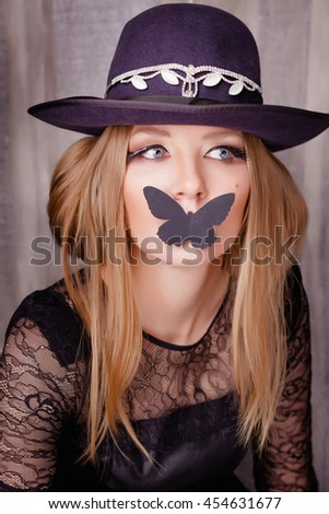 Portrait of a beautiful young girl in a black dress with lace, hat, butterfly