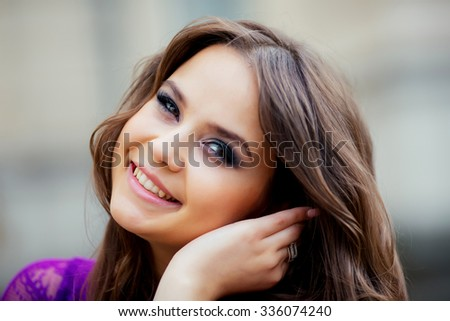 portrait of a beautiful young girl in a blue dress posing against the backdrop of the old building - stock photo