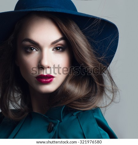 Portrait of a beautiful young girl in a blue hat with expressive eyes