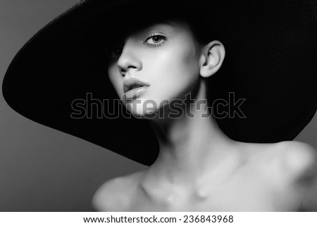 Portrait of a beautiful young girl in a hat, black and white photography in the studio - stock photo