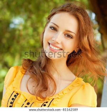 portrait of a beautiful young girl in a park on a background of green nature - stock photo