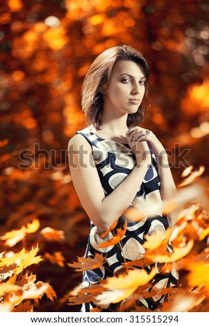 Portrait of a beautiful young girl in a positive mood calm against a bright golden autumn in park - stock photo