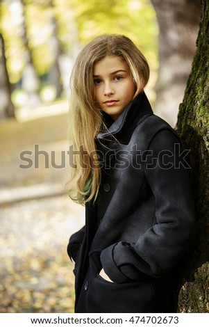 Portrait of a beautiful young girl in autumn park.