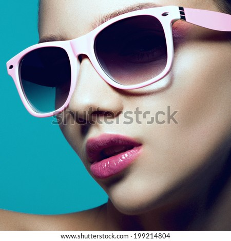 Portrait of a beautiful young girl in studio with sunglasses on a blue background, close up