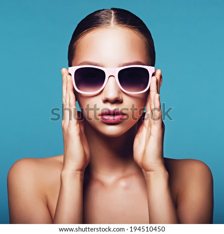 Portrait of a beautiful young girl in sunglasses on a blue background - stock photo