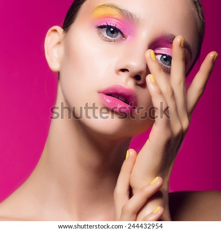 Portrait of a beautiful young girl in the studio on a pink background with colorful makeup, closeup - stock photo