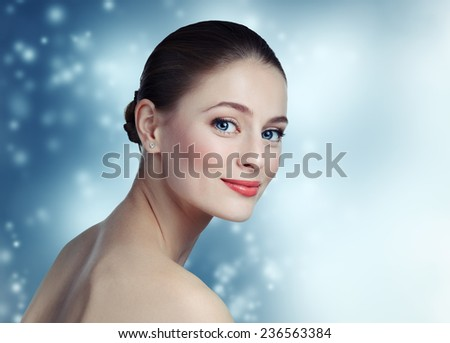 Portrait of a beautiful young girl model with clean skin and blue eyes on winter background. Looking at the camera. Pose in a half-turn. Cold toning. - stock photo