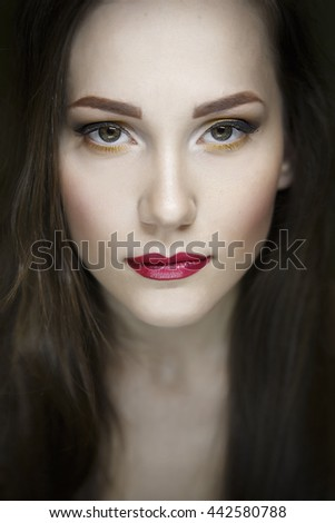 Portrait of a beautiful young girl on a dark background - stock photo