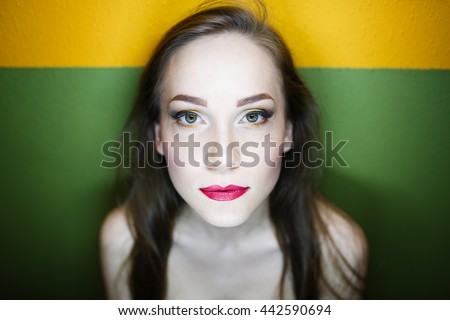 Portrait of a beautiful young girl on background of two colors orange green