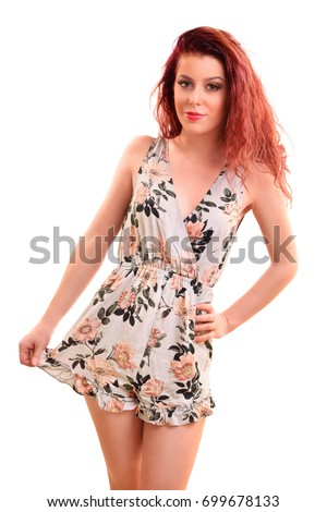 Portrait of a beautiful young girl smiling, holding her dress and posing, isolated on white background.