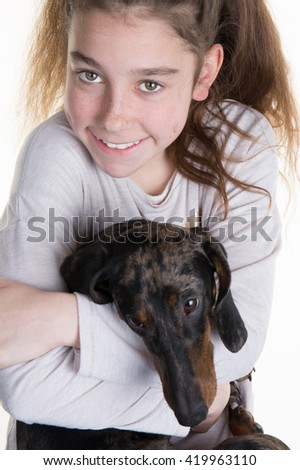 Portrait of a beautiful young girl snuggling with a  puppy dog, isolated on white in studio