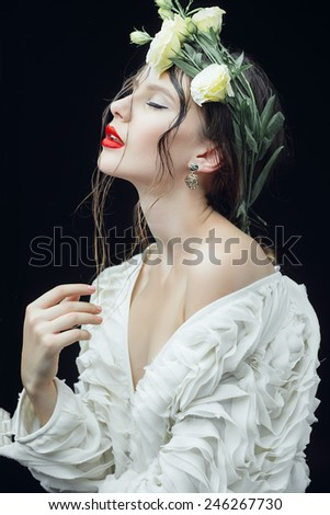 Portrait of a beautiful young girl with a wreath of flowers on her head - stock photo