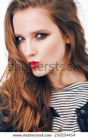 Portrait of a beautiful young girl with bright make-up in the studio in a rock style shows kiss