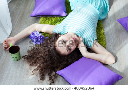 Portrait of a beautiful young girl with brown curly hair. Drink your morning coffee. Big green eyes. Pillows purple. Girl lying on the floor on a mat for meditation and looking at camera.  - stock photo