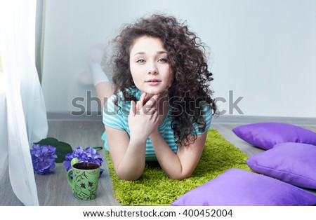 Portrait of a beautiful young girl with brown curly hair. Drink your morning coffee. Girl lying on the floor on a mat for meditation and looking at camera. Big green eyes. Pillows purple. - stock photo