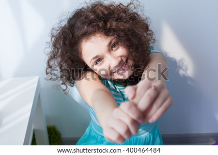 Portrait of a beautiful young girl with brown curly hair. Fun and joy. Happy girl in the morning sun is smiling at the camera. Delicate blue dress. - stock photo
