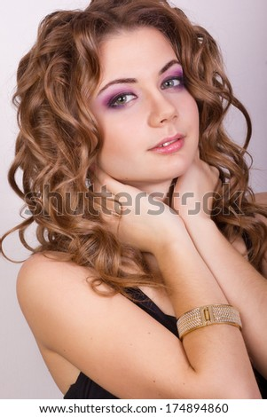 Portrait of a beautiful young girl with brown curly hair in a tight black dress and a gold bracelet on his wrist