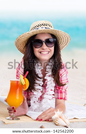 Portrait of a beautiful young girl with cocktail on the beach