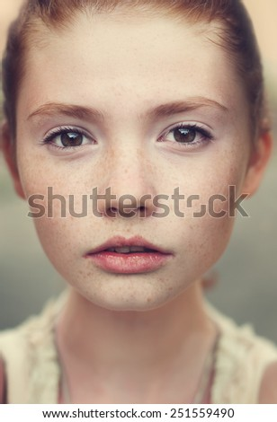 portrait of a beautiful young girl with freckles - stock photo