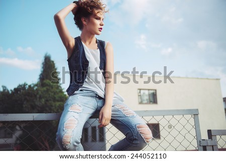 Portrait of a beautiful young girl with long curly hair, sitting on the fence, life style - stock photo