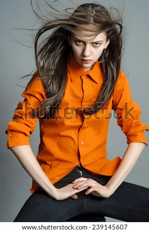 portrait of a beautiful young girl with long hair flying in the orange shirt