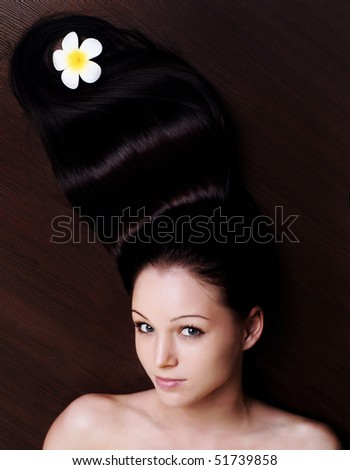 portrait of a beautiful young girl with long hair on a brown background - stock photo