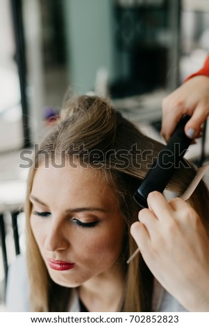 Portrait of a beautiful young girl with makeup makes hair styling in the salon