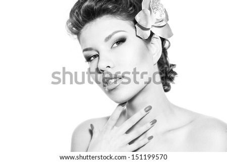 Portrait of a beautiful young girl with perfect make-up and nails, with a flower in her hair, black and white