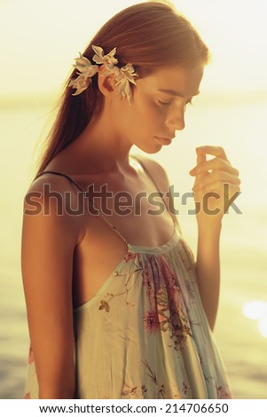 Portrait of a beautiful young girl with red hair, walking along the beach in a summer dress - stock photo