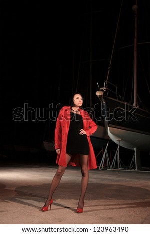 portrait of a beautiful young girl with red jacket in small marina at night - stock photo
