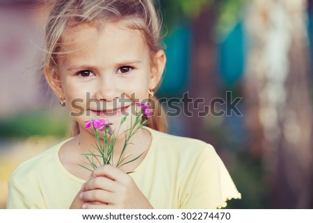 portrait of a beautiful young girl with wildflowers at the day time - stock photo