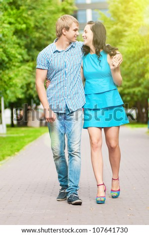 Portrait of a beautiful young happy smiling couple - walking at green park outdoor - stock photo