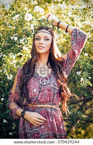Portrait of a beautiful young hippie girl among the flowers - stock photo