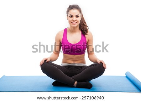 Portrait of a beautiful young Hispanic woman sitting on a mat and ready to do some yoga