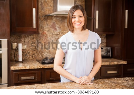 Portrait of a beautiful young housewife standing in her kitchen and smiling - stock photo