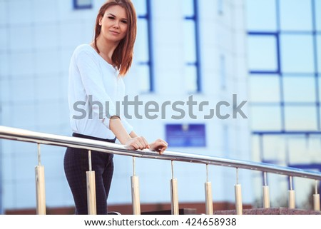 Portrait of a beautiful young lady in business informal dress on a background of the business center. The informal business, free business concept - stock photo