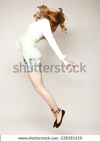 Portrait of a beautiful young lady jumping in joy over grey  background