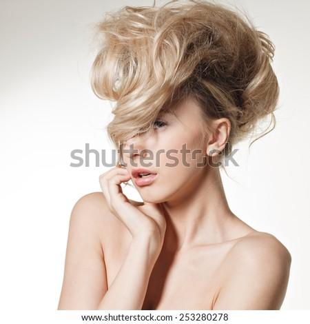 Portrait of a beautiful young lady smiling with a long fair hair posing  in studio.  - stock photo